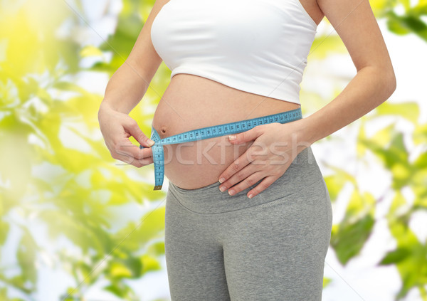 close up of pregnant woman measuring her tummy Stock photo © dolgachov
