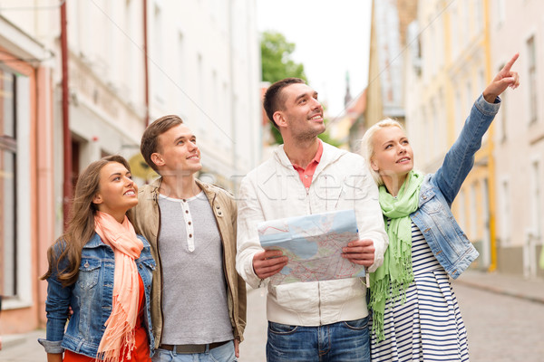 group of smiling friends with map exploring city Stock photo © dolgachov