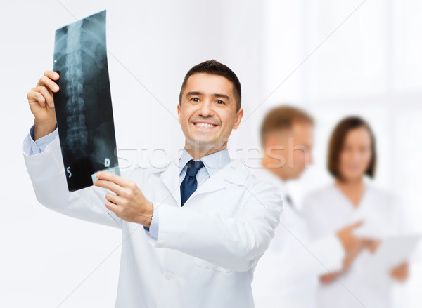 smiling male doctor holding x-ray at hospital Stock photo © dolgachov