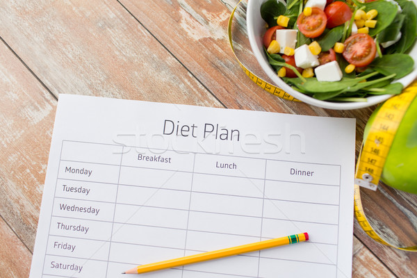 close up of diet plan and food on table Stock photo © dolgachov