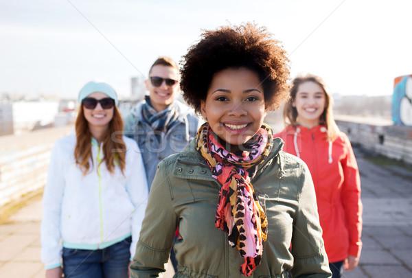 group of happy teenage friends on city street Stock photo © dolgachov