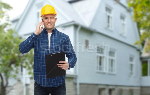 smiling builder in helmet calling on smartphone Stock photo © dolgachov