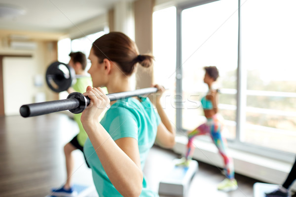 close up of people exercising with bars in gym Stock photo © dolgachov