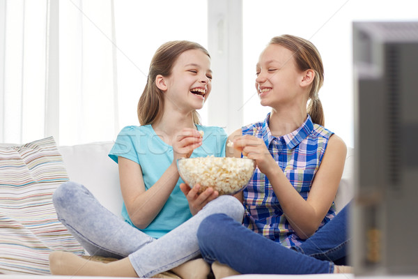 happy girls with popcorn watching tv at home Stock photo © dolgachov