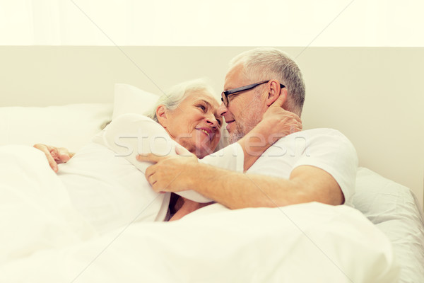 Stock photo: happy senior coupler lying in bad at home