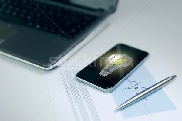 close up of smartphone with lightbulb on screen Stock photo © dolgachov