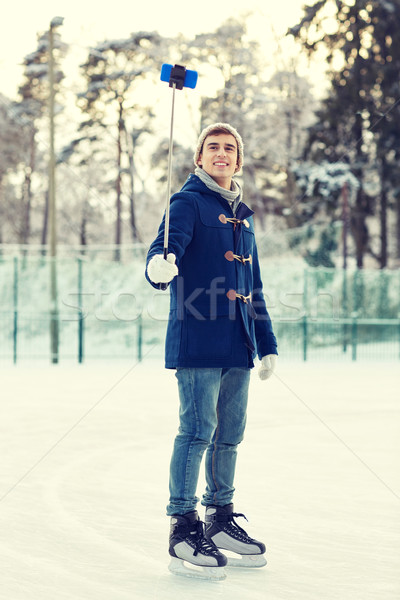 happy young man with smartphone on ice rink Stock photo © dolgachov