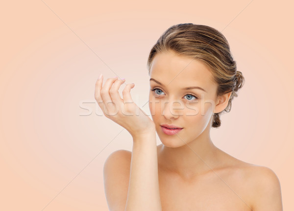 woman smelling perfume from wrist of her hand Stock photo © dolgachov