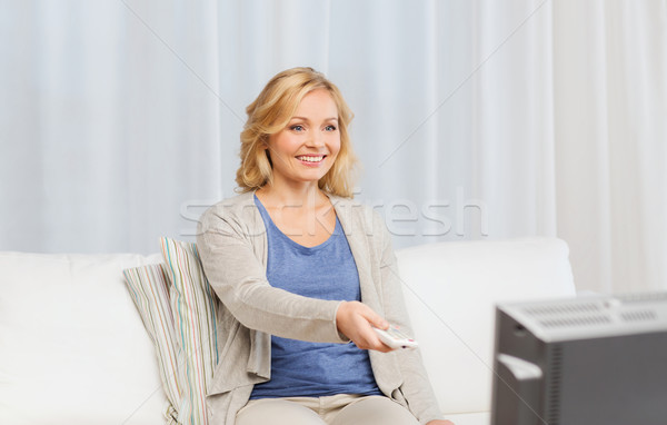 woman with remote control switching tv at home Stock photo © dolgachov