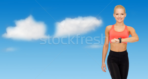 smiling woman with heart rate bracelet on hand Stock photo © dolgachov