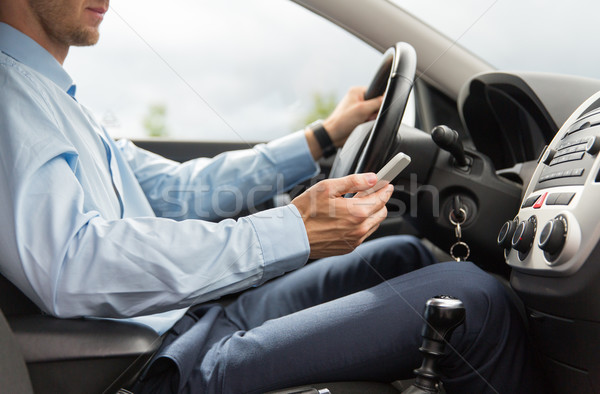 Stock photo: close up of man with smartphone driving car