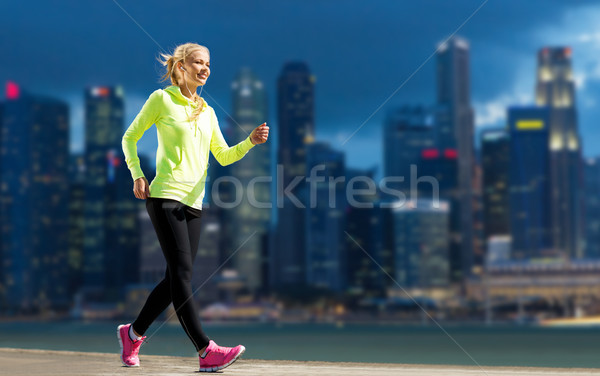 happy woman jogging over city street background Stock photo © dolgachov