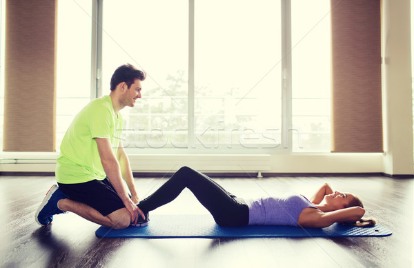 woman with personal trainer doing sit ups in gym Stock photo © dolgachov