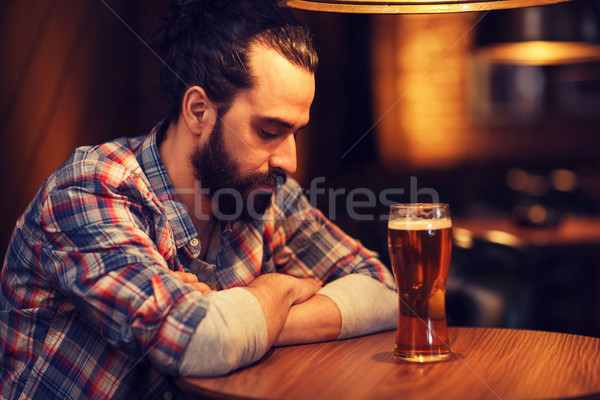 unhappy lonely man drinking beer at bar or pub Stock photo © dolgachov