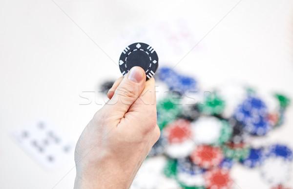 close up of male hand holding casino chip Stock photo © dolgachov