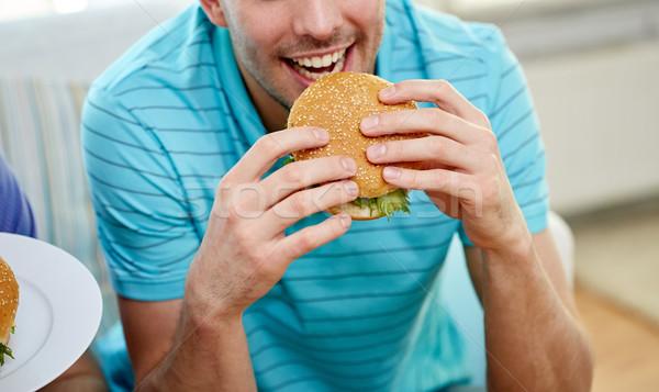 close up of happy man eating hamburger at home Stock photo © dolgachov