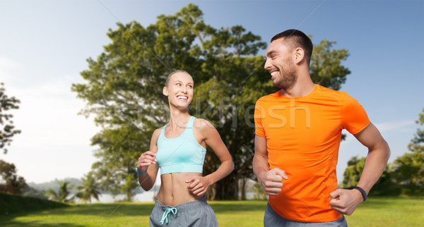 smiling couple running over summer park background Stock photo © dolgachov