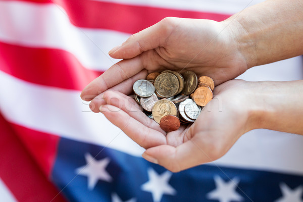 Stock photo: close up of hands with coins over american flag