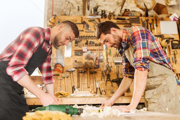 carpenters with blueprint at workshop Stock photo © dolgachov