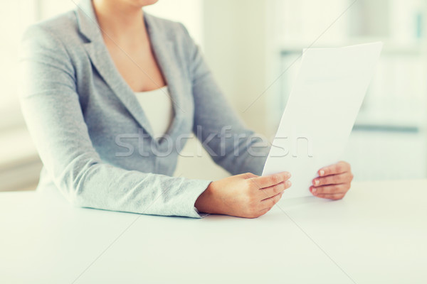 Stock photo: close up of woman reading papers or tax report