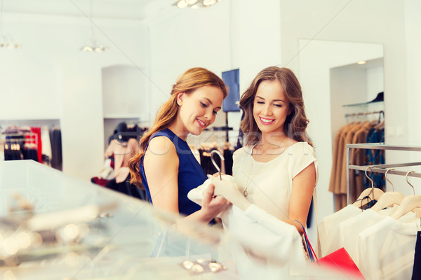 Stock photo: happy women with shopping bags at clothing shop