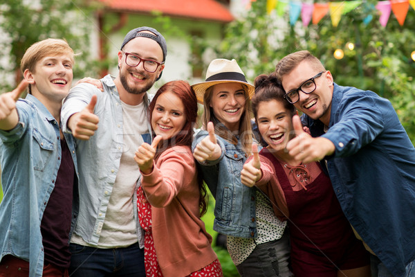 happy friends showing thumbs up at summer garden Stock photo © dolgachov