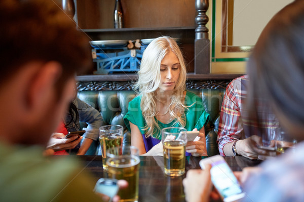 friends with smartphones and beer at bar or pub Stock photo © dolgachov