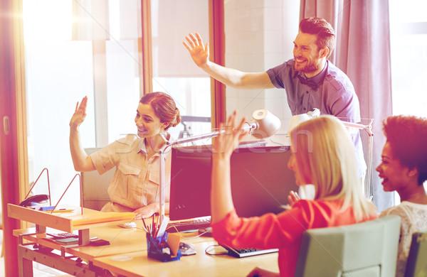 happy creative team waving hands in office Stock photo © dolgachov