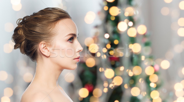 beautiful young woman face over christmas lights Stock photo © dolgachov