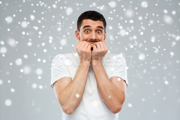 scared man in white t-shirt over snow background Stock photo © dolgachov