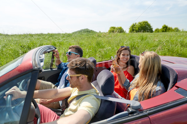 happy friends driving in cabriolet car with beer Stock photo © dolgachov
