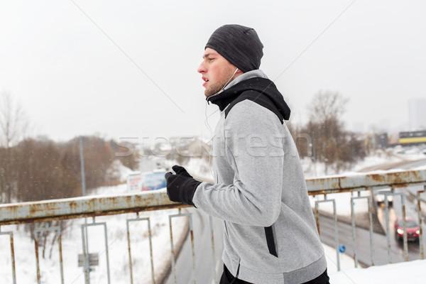 man in earphones running along winter bridge Stock photo © dolgachov