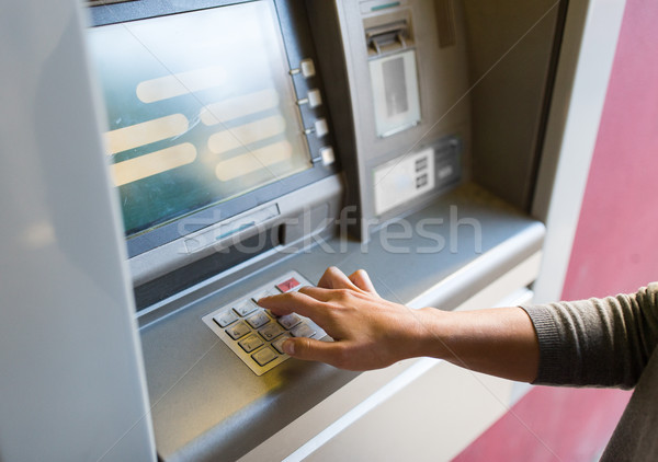 Stock photo: close up of hand entering pin code at atm machine