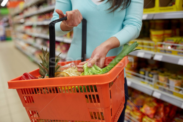 woman with food basket at grocery or supermarket Stock photo © dolgachov