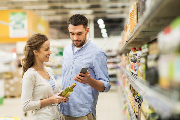 couple with smartphone buying olive oil at grocery Stock photo © dolgachov