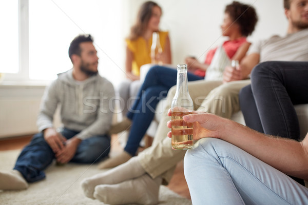 close up of man with beer bottle and friends Stock photo © dolgachov