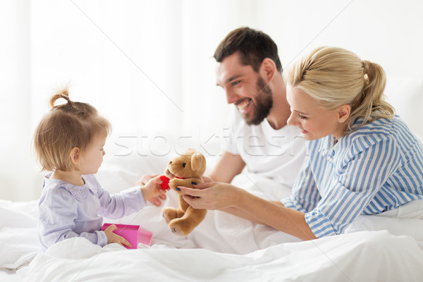 happy family with gift box in bed at home Stock photo © dolgachov