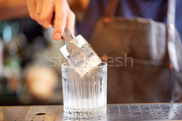 bartender adding ice cube into glass at bar Stock photo © dolgachov