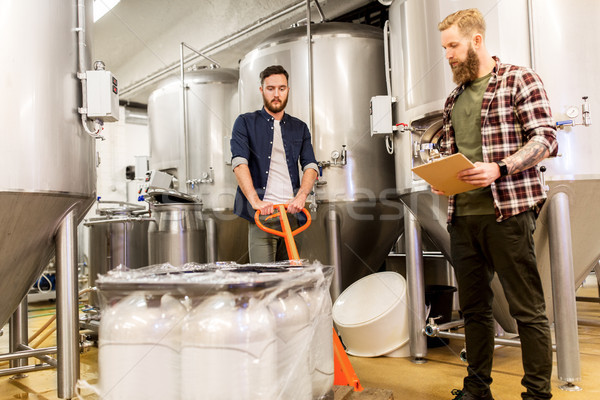 Stock photo: men with malt and clipboard at craft beer brewery