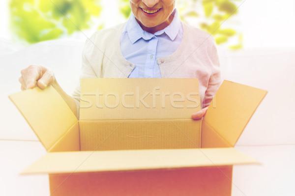 close up of senior woman with parcel box at home Stock photo © dolgachov