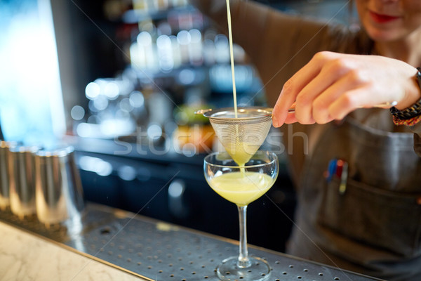 bartender pouring cocktail into glass at bar Stock photo © dolgachov