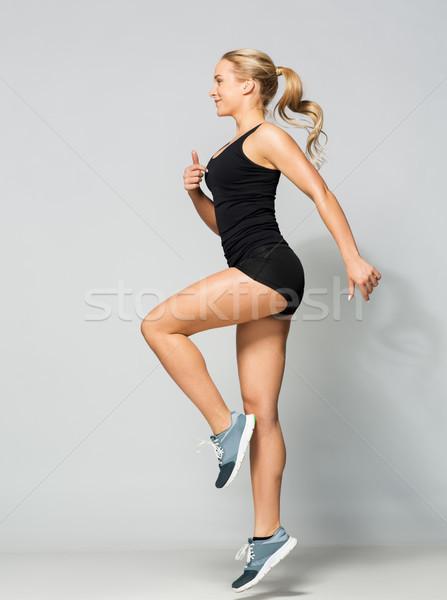 Młoda kobieta czarny odzież sportowa skoki sportu fitness Zdjęcia stock © dolgachov