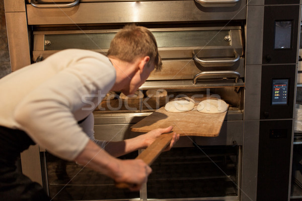 baker putting dough into bread oven at bakery Stock photo © dolgachov