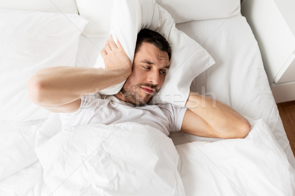 Człowiek bed poduszkę cierpienie hałasu ludzi Zdjęcia stock © dolgachov