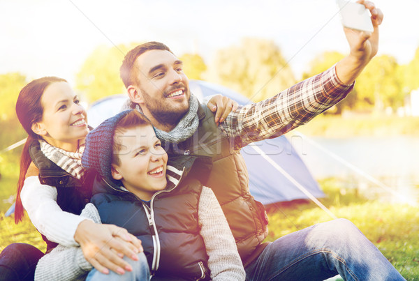 family with smartphone taking selfie at campsite Stock photo © dolgachov
