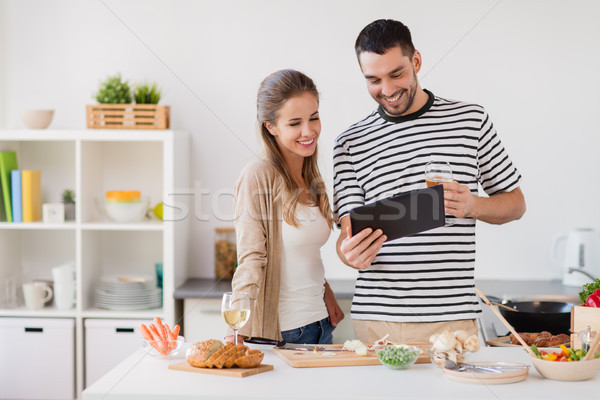 happy couple with tablet pc cooking food at home Stock photo © dolgachov