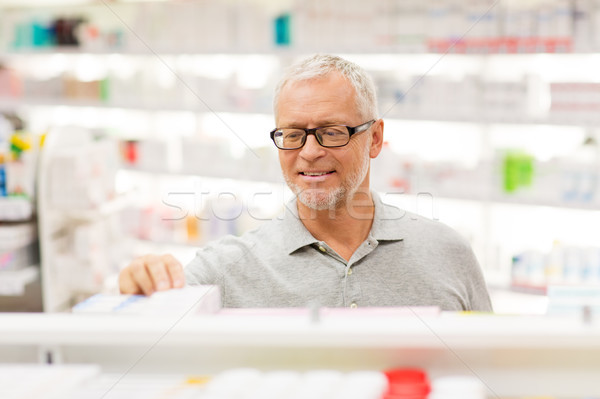 senior male customer with drug at pharmacy Stock photo © dolgachov