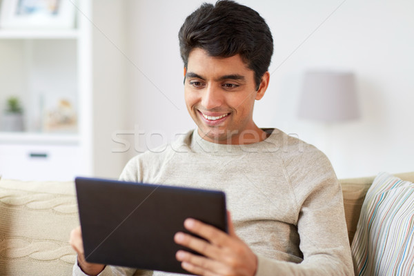 smiling man with tablet pc at home Stock photo © dolgachov