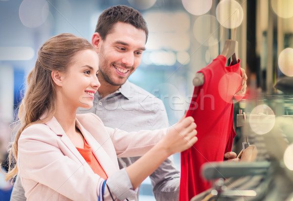 happy young couple choosing dress in mall Stock photo © dolgachov