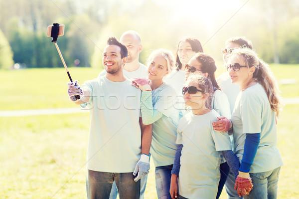 group of volunteers taking smartphone selfie Stock photo © dolgachov